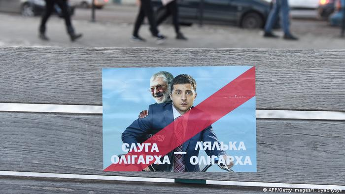An anti-Zelensky sticker shows him with Kolomyskyi, with the caption reading Servant of the oligarch - Puppet of the oligarch (AFP/Getty Images/Y. Dyachysyn)