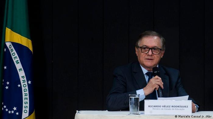 Ricardo Vélez Rodríguez fala ao microfone, em uma mesa. Ao lado dele, está a bandeira do Brasil