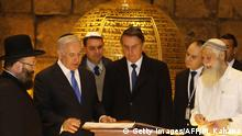 01.04.2019 *** Brazilian President Jair Bolsonaro (C) listens to Israeli Prime Minister Benjamin Netanyahu (2nd-L) near the Rabbi of the Western Wall Shmuel Rabinovitch (L) and Bolsonaro's son Fabio (3rd L) during a visit to a synagogue inside the Western Wall Tunnels in Jerusalem's Old City on April 1, 2019. (Photo by Menahem KAHANA / POOL / AFP) (Photo credit should read MENAHEM KAHANA/AFP/Getty Images)