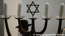 a menorah including four candles and centered by the Star of David