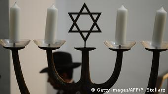 A man walks past a menorah in Cologne's synagogue