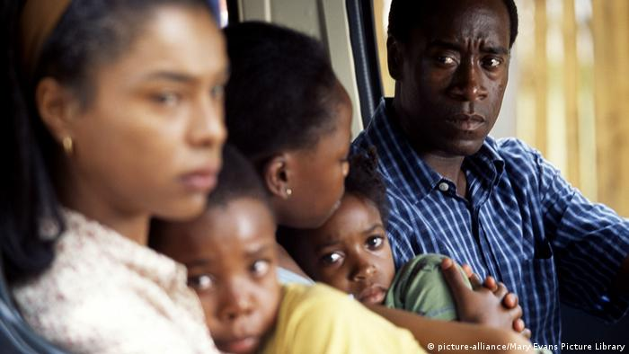 Film still from Hotel Rwanda: A man sitting with two women and two scared children in a car (picture-alliance/Mary Evans Picture Library)
