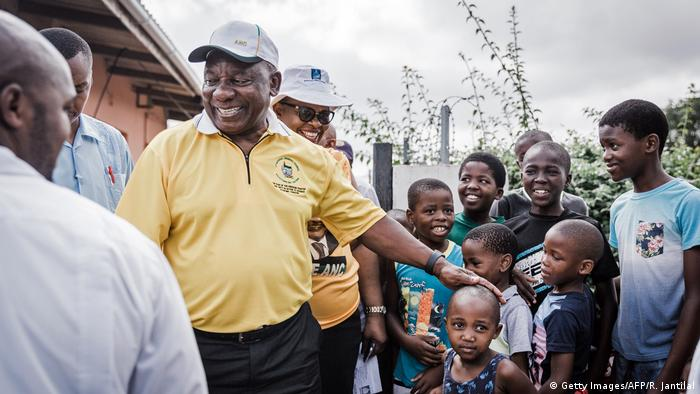 Cyril Ramaphosa, dressed casually in a polo shirt and cap, greets young local residents during a door to door campaign visit
