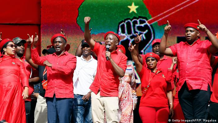 Julius Malema and other EFF leaders raise their arms while singing