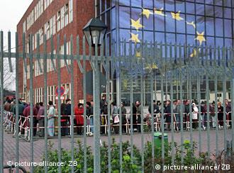 People wait in line in front of an EU flag