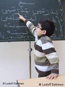 Ein Schüler zeigt mit dem rechten Zeigefinger auf ein arabisches Schriftzeichen(Foto: Ludolf Dahmen)