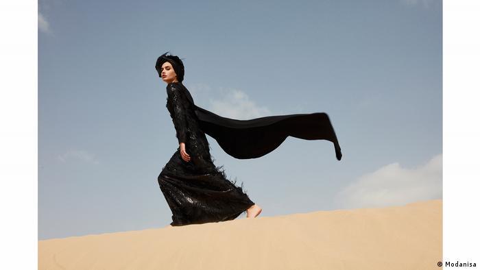 Eine Frau im schwarzen Kleid mit wehemdem Schal geht über eine Wüstendüne (Modanisa)