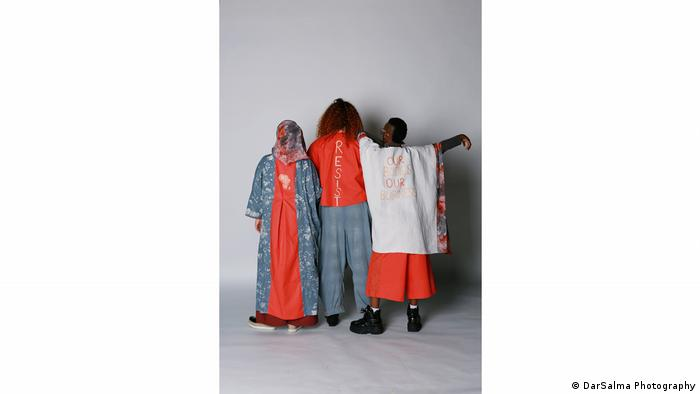 Three people turning their backs to the camera, fashion designs by Naomi Afia (DarSalma Photography)