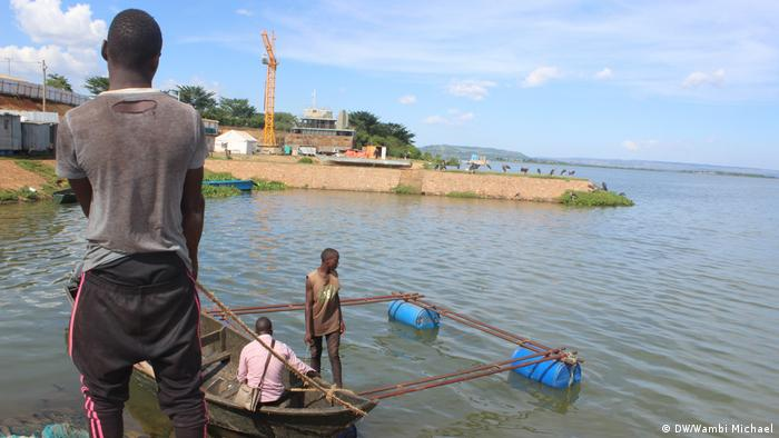 A man holds the rope of a boat in shallow water