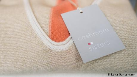 Close-up of a beige cashmere pullover with the cashmere sisters gray label hanging on it (Foto: Lena Ganssmann)