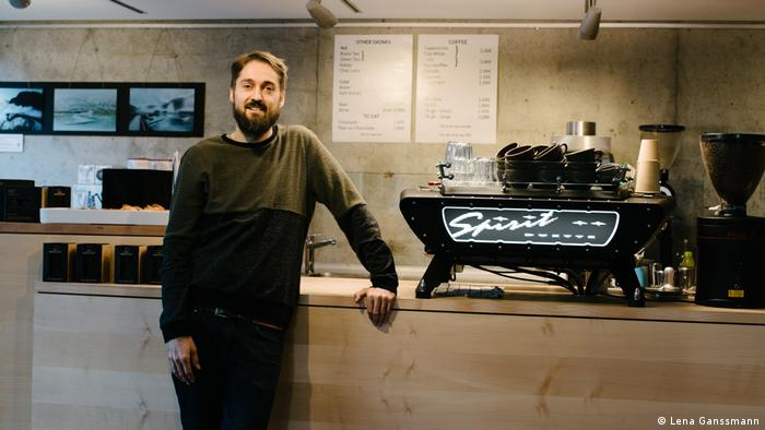 Kristian Moldskret leans on a wooden counter next to his coffee machine. (Foto: Lena Ganssmann)