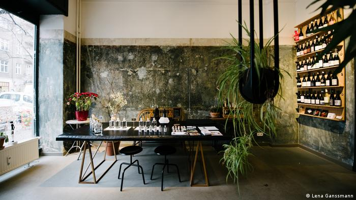 bottles lined up on a wall and a table with a plant in the foreground (Foto: Lena Ganssmann)