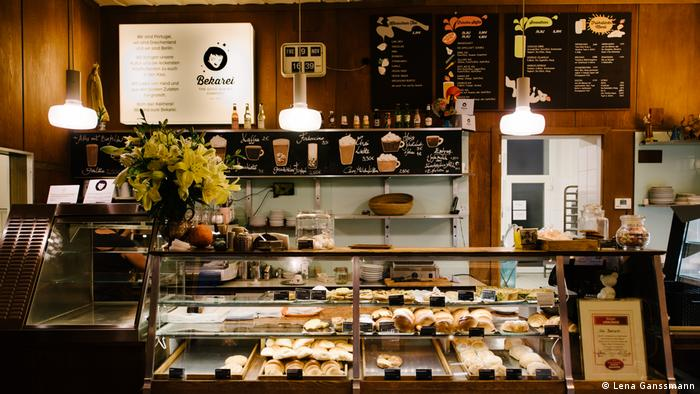bakery counter, prominent retro clock of the back wall, wood paneling and brown tile floor (Foto: Lena Ganssmann)