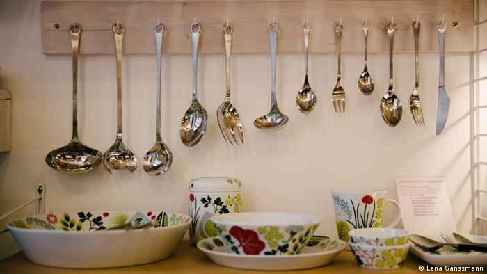 White porcelain bowls, cups and cans with colorful pictures of vegetables and berries. Silver ladles, cables, spoons and knives are hanging above (Foto: Lena Ganssmann).