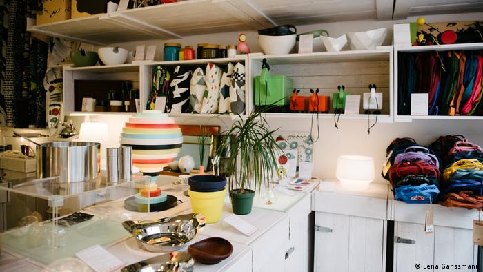 A sales room with white chests of drawers and shelves with various bowls, pots, table lamps, cushions and rucksacks (Foto: Lena Ganssmann).