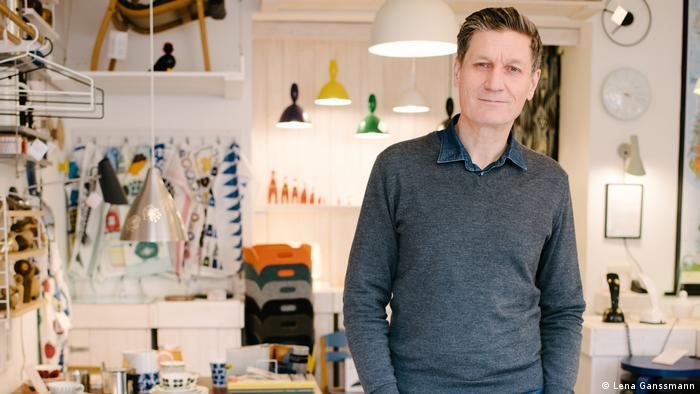 Sten Rasmussen in a gray v-neck pullover in his shop with a variety of colorful lamps in the background (Foto: Lena Ganssmann)