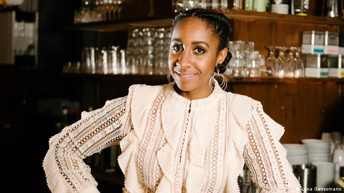Jeniffer Mulinde-Schmid aka Black Heidi in cream-colored long-sleeved blouse standing at a bar (Foto: Lena Ganssmann).