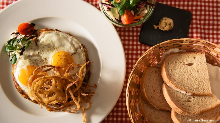 White porcelain plate with rösti and two fried eggs as well as roasted onions on a red and white checkered tablecloth, next to a basket of white bread(Foto: Lena Ganssmann).
