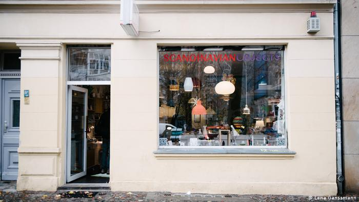 Exterior of the Scandinavian Objects store, the glass exterior door is open, with illuminated window lamps visible in the window (Foto: Lena Ganssmann).