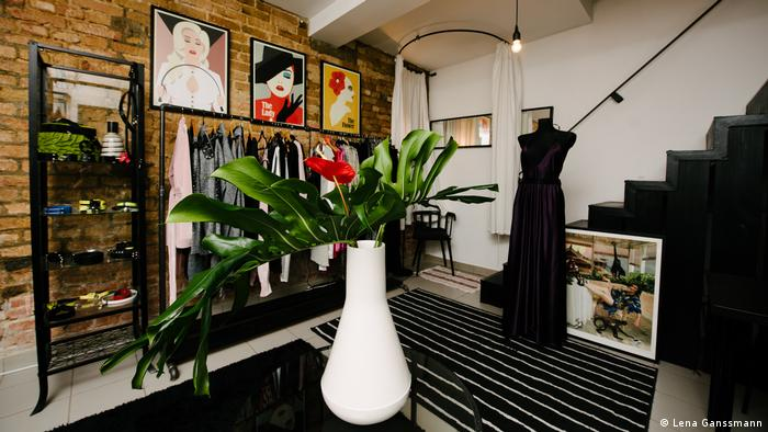 Interior of the shop, in the center stands a white vase with a big green leaf and red flower, in the background a dress stand with clothes. (Foto: Lena Ganssmann)