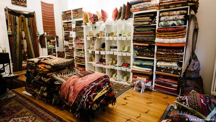 Interior of the shop, the middle piled with colorful rugs, on the walls shelves are colorful textiles and laurel soaps (Foto: Lena Ganssmann)
