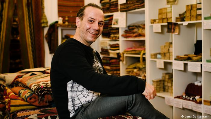Owner John Al Haddad sits on a pile of colorful rugs, with shelves of laurel soaps and other textiles in the background. (Foto: Lena Ganssmann)