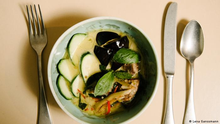 Curry with zucchini and eggplant slices in milky sauce in a mint-colored plate, left and right next to it is cutlery. (Foto: Lena Ganssmann)