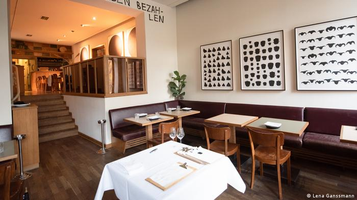 Entrance of the restaurant with square tables and chairs, on the walls is an upholstered bench (Foto: Lena Ganssmann)
