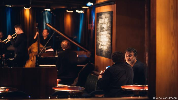 patrons sit at tables and in the background a trumpeter, double bassist and pianist play(Foto: Lena Ganssmann).