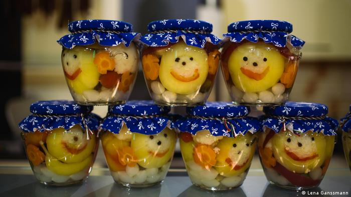 Pickled yellow and orange vegetables, with lids made of blue-colored fabric with white bows.(Foto: Lena Ganssmann)