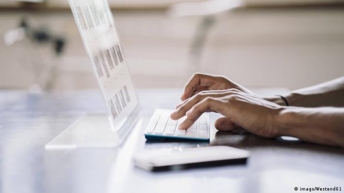 Mão digita em computador