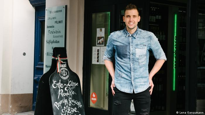 Lázsló Baksa stands in front of a shop door in a denim shirt, arms on his hip. Next to him a blackboard in the form of a bottle (Foto: Lena Ganssmann).