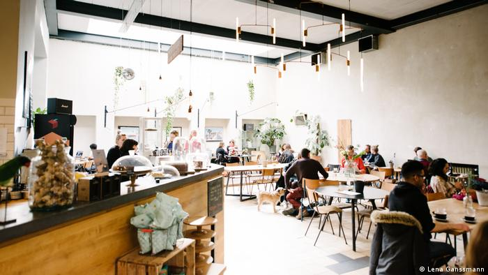 Partly occupied tables and chairs made of wood, ceiling lamps, left is a bar with cake. (Foto: Lena Ganssmann)