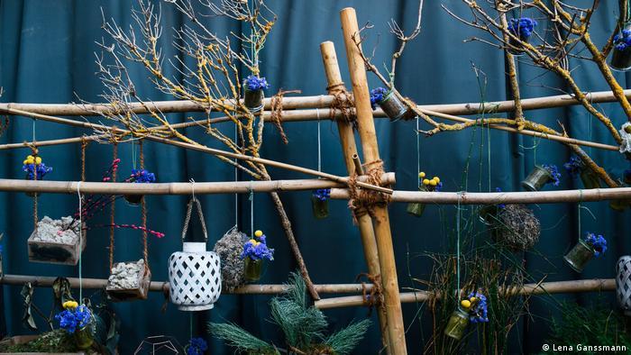 Dekoration aus Bambusstäben mit lila und gelben Blumen, getrockneten Ästen und Lampions. (Foto: Lena Ganssmann)