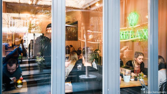 Exterior view of Dudu Restaurant through windows, which is densely packed with people sitting at narrow wooden tables. (Foto: Lena Ganssmann)