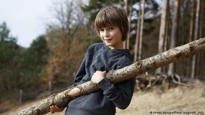 A boy carrying a large log in a woodland clearing (Imago Images, Stop Images, M Volk)