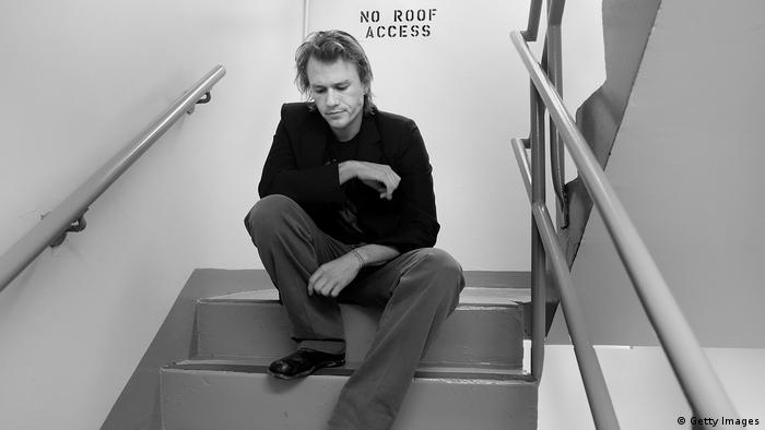 Black and white photo of Heath Ledger seated on the steps of a stairway.