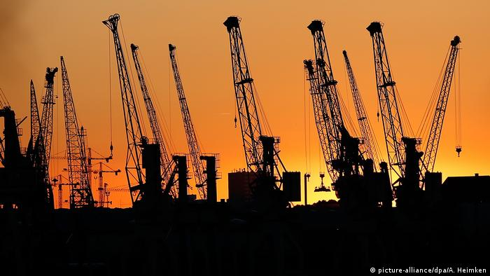 Guindastes de porto vistos a contraluz sobre céu alaranjado