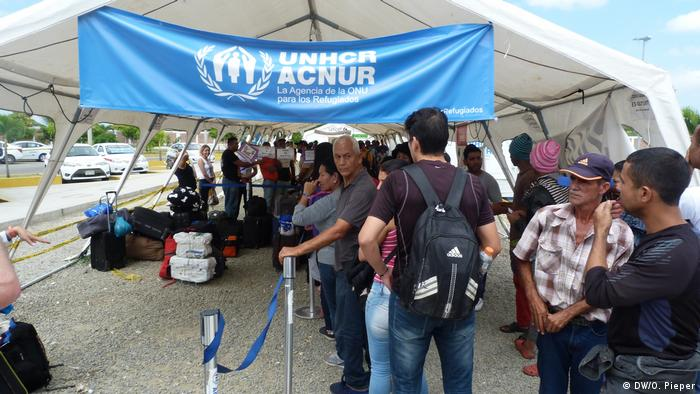 Venezuelan refugees stand outside a UNHCR aid tent after arriving in Tumbes in Peru.