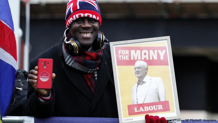 A protester holding a poster depicting Labour leader Jeremy Corbyn