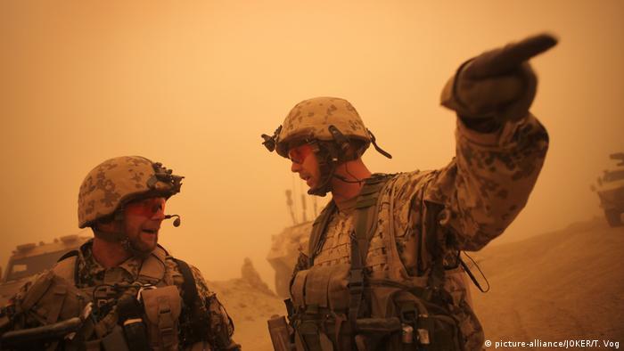 German troops in Afghanistan against an orange sky