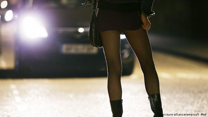 Проститутка стоит на дороге перед машиной со включенными фарами