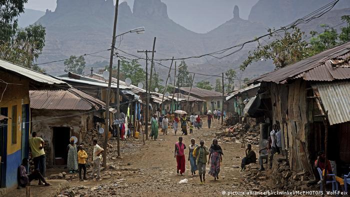 Menschen stehen an oder laufen auf einer unbefestigten Straße, die von Wellblech bedeckten Häusern gesäumt ist, in einem Dorf in Äthiopien