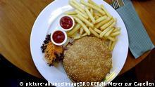 Hamburger mit Sesambrötchen, Pommesfrites und Ketchup auf einem Teller