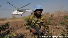 ARCHIV 2009****A UN Ghanaian peacekeeper in Ivory Coast (ONUCI) exits from an army helicopter to take part in military manoeuvers at Bouna airport on January 13, 2009. They simulate the take over of the airport as part of security measures ahead of the general elections. Ivory Coast has put off presidential elections several times since President Laurent Gbagbo's mandate ran out in October 2005, the most recent postponement from a planned date of November 30. Ivory Coast, the world's top cocoa grower and a former French colony, was sliced in half after a September 2002 coup attempt against President Laurent Gbagbo. AFP PHOTO/ KAMBOU SIA (Photo credit should read KAMBOU SIA/AFP/Getty Images)