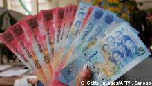 ARCHIV 2007****Accra, GHANA: A woman holds 03 July 2007 in Accra a wad new currency, the new cedi, that Ghana put in circulation that day, although the old money will still be valid until the end of the year. Currently, the cedi is one of the least valued currencies in Africa: 9000 cedis equal one US dollar. Ernest Addison, head of research at the Bank of Ghana, assured in November 2006 that the changeover was not a revaluation nor devaluation, and will not affect foreign exchange. AFP PHOTO / ISSOUF SANOGO (Photo credit should read ISSOUF SANOGO/AFP/Getty Images)