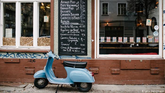 A blue motor scooter out front of a restaurant (Lena Ganssmann)