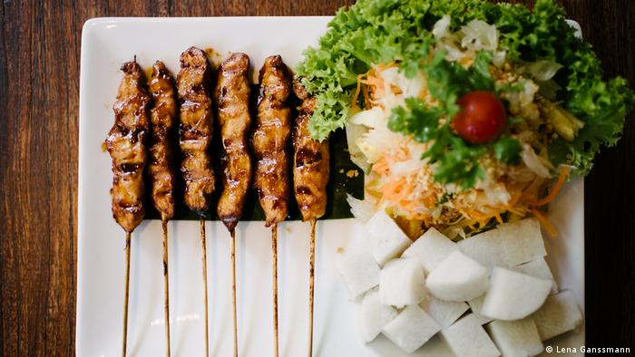 hicken skewers with rice cake, salad and homemade peanut sauce (Lena Ganssmann)