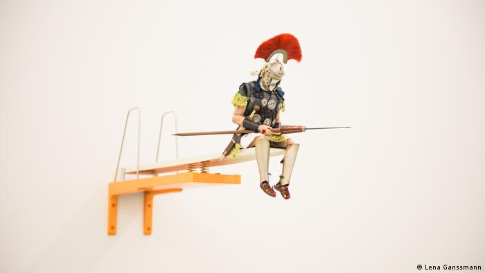A soldier sits on a miniature diving board and looks at his mobile phone (Lena Ganssmann)