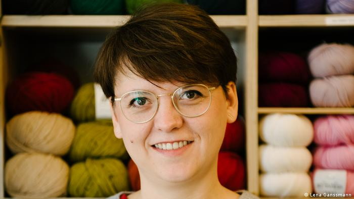 Ruta Sluskaite-Dittmann with short dark brown hair and glasses in front of a shelf with balls of wool. (Foto: Lena Ganssmann)